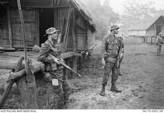 Australian Army Training Team Vietnam (AATTV) adviser, Captain Peter Shilston of Williamtown, NSW (left), and an American adviser look on while Montagnard soldiers of the 1st Battalion, 2nd Mobile Strike Force search a village during an operation in central South Vietnam. Capt Shilston is commander of the Battalion which operates out of Pleiku. South Vietnam - July, 1970