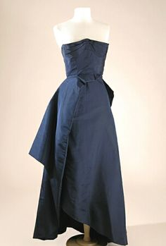 Schiaparelli Couture Navy Taffeta Two-Piece Evening Dress   French, circa 1950   Comprising skirt with asymmetrical side drape hem, strapless bodice with pleated stand away bustline and attached asymmetrical winged peplum overskirt, size 4
