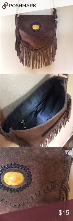 """Bohemian Brown Leather Purse w/ Tassles Super cute leather purse with adjustable shoulder strap. One large compartment and one small zippered compartment on the inside. Measures about 10"""" wide. Black cotton liner. Has one of the wrap around leather strings torn, as depicted in the photo. Bags Shoulder Bags"""