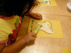 """Kid crafts: brushing the tooth white again with """"toothpaste"""" (white paint)"""