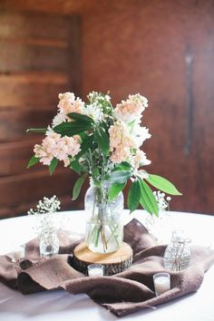 the bucolic centerpiece  A rustic arrangement with fresh florals and dainty details pair effortlessly with the rustic elements of the base.
