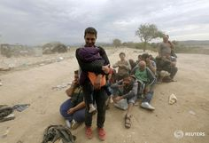 Syrian father protects his child from gusts of wind and dust as they wait to cross to FYRO Macedonia.Yannis Behrakis