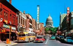 """State Street in Madison, Wisconsin, in late summer of 1956.  Marilyn Monroe stars in her """"new hit movie"""" - Bus Stop (released August 31, 1956).  Ironically, a classic old bus is at a bus stop at the corner.  (I rode these almost daily as a kid through my teens, the the color scheme was different in my hometown.)  And how many theaters across the country in the 50s were named """"Orpheum""""?!  Montgomery Wards?  Long gone."""