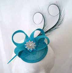 Elegant Turquoise Blue Curl Feather Sinamay Mini Hat , £36.50 Order Now from www.indigodaisyweddings.co.uk Specialising in stunning bespoke cocktail fascinators and formal hats in a wide range of colours, perfect for Royal Ascot and The Kentucky Derby. Plus all your wedding floral accessories including shoe clips, vintage flapper bands, feather and flower fascinators, feather fans, fairy wands, wrist corsages, wedding bouquets & buttonholes. Worldwide Delivery.