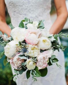 White and blush peonies were the focal point of this delicate bouquet, along with thistle, dusty miller, and small gray feathers.
