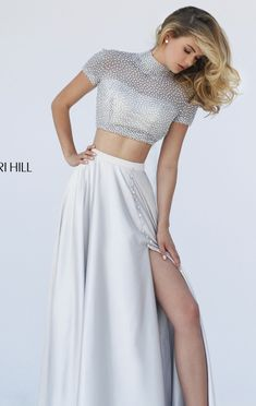 Add a modern vibe to your stylish look in this two-piece set gown, Sherri Hill 50037. High neckline with short sleeves feature this ethereal long gown. Tiny beads scattered allover the crop top with keyhole opening at the back shows a peek of your magnificent skin. Full skirt drops down to a full length finish with the daring side slit finishes the powerfully alluring look.