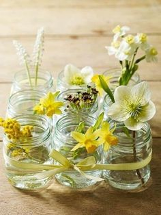 Clustering mason jars together with very simple  single stem flowers is both a cheap and pretty way to theme a table. Love the idea of a simple ribbon holding it all together and how fast can this be made??