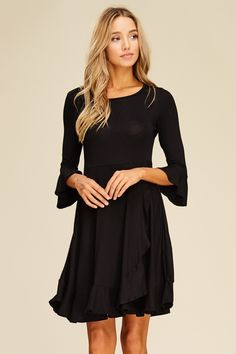 "Short Wrap Dress with Ruffle Hem Style# D5323  Knit dress featuring solid, round neck, 3/4 bell sleeve, wrap, layered, ruffle hem, short, loose, relaxed, soft and snug material.  Rayon Spandex  Hand Wash Recommended  Model is 5'8"" tall and wearing size S     32"" Bust, 24"" Waist and 33.5"" Hips  FABRIC CONTENT 95% RAYON 5% SPAN COUNTRY OF ORIGIN UNITED STATES BLACK"