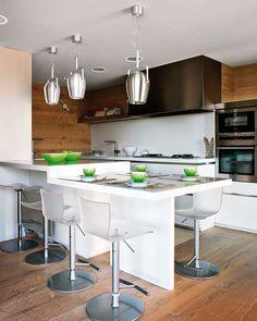 Cozinha planejada moderna com móveis em inox, balanceando com materiais rústicos como a madeira. As luminárias, cadeiras, forno e armário em inox dão o charme especial. http://belacozinha.com/cozinhas-decoradas-para-apartamento-e-casas/