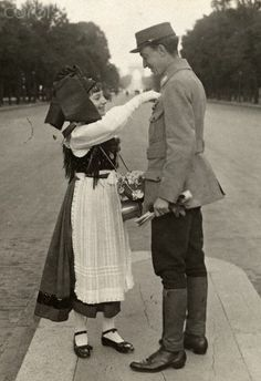 A young girl pins a flower on a World War I French soldier. - 42-32920520 - Rights Managed - Stock Photo - Corbis