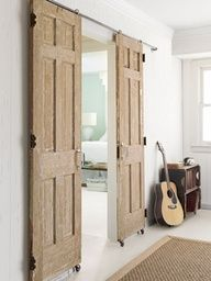 ~ DIY ~Instead of buying an expensive barn door track kit, make one yourself. Fifty-eight dollars worth of hardware—including casters and plumbing pipes—transformed two salvaged doors into a barn-style entry. Salvaged Doors, Old Doors, Sliding Doors, Repurposed Doors, Entry Doors, Wooden Doors, Patio Doors, Sliding Cupboard, Sliding Room Dividers