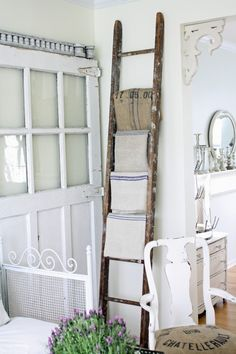 Problem: small bathroom is narrow and has only small bits of free floor space for storage units - Solution: ladder as repurposed towel rack, hang it up high on the wall past the tiles, stick some dowling at the bottom to lift the base of the ladder slightly away from the wall. Or do the same *but horizontally* above the bidet..