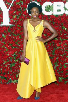 Danai Gurira stuns at the 2016 Tony Awards in a ladylike yellow gown with asymmetrical hem by Rosie Assoulin.