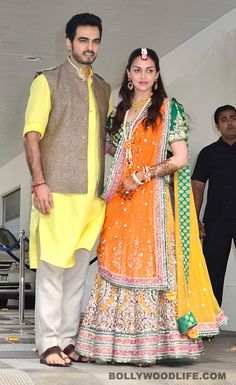 Esha Deol opts for a Neeta Lulla creation for her mehndi ceremony : Posing for the shutterbugs with beau Bharat Takhtani, Esha looked super ecstatic. Her forearm and her palms were suffused with mehndi and she showed it off with a hint of glow on her face  While Ms Deol left her hair loose and posed in a bright orange-yellow lehenga choli, Bharat was seen in a simple kurta teamed with an ethnic Nehru jacket. Quite an antithesis to his previous wedding ensembles;