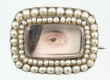 Lover's eye miniature hand-painted on ivory surrounded by a double row of pearls.  Brown eye of a lady with brown hair painted down the side of her face.  Circa 1820.