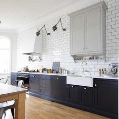 cuisine noir et blanc aménagée avec des armoires noires, un carrelage métro blanc et deux appliques murales de style industriel