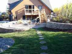 Use a slope to your advantage in your landscape. Rock walls create a level area for a patio and fire pit, while also surrounding it with shrub beds and perennials. Lakeside Cottages by Creative Landscape & Design.