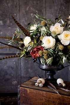 Gorgeous over flowing fall flower arrangement with pheasant feather accents