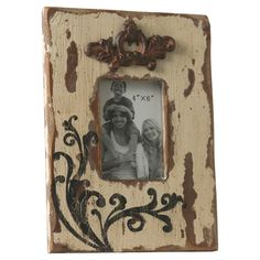 Distressed photo frame with scrolling accents.    Product: Photo frameConstruction Material: Wood, metal and glass