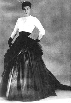 Lucky is wearing an evening gown by Christian Dior    A simple white linen bolero relieves the full-skirted gown of  draped black chiffon taffeta, in the model 'Meilhac', from the Haute Couture  Collection, Spring/Summer 1952. Archives Christian Dior