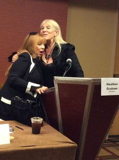 Author Heather Graham and M.J. Rose caught in an embrace at the podium at ThrillerFest14.