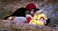 By: David Leeson 2004 Pulitzer Prize Winner - (Breaking News Photography) - Caught in crossfire from the 3rd Intantry Division fighting through Northern Baghdad, a woman huddles in an open ditch with two terrified and bloodstained children.