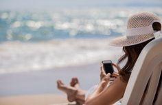 Mujer en la playa con el móvil