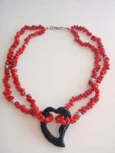 """BELLA BOHEMIAN BOUTIQUE - A very stylish necklace made with red coral nuggets, doubled on both sides and suspended from the middle of the black lava-stone heart pendant, which is embellished with sterling silver Balinese beads. Finished with sterling silver """"S"""" clasp, looks lovely around the neck, light weight. - 68 USD"""