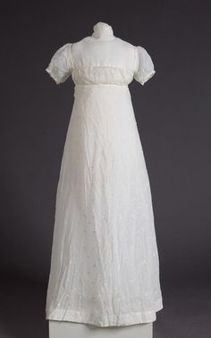 Embroidered white muslin dress, ca. 1810. Embroidery  is a repeated knotted design of circles and quarter moons.