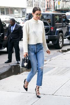 Bella Hadid wears a mock neck cable knit sweater, straight leg denim, and pointed-toe lace-up heels