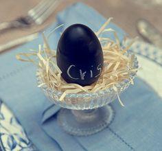 O lugar na mesa, aqui, é marcado com um ovinho de madeira pintado com tinta de lousa. A palhinha dá um ar de ninho à decoração