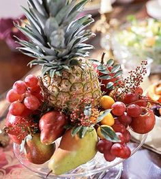 Fresh produce -- grapes, pears, apples, and kumquats -- circle around a center pineapple placed on a footed cake stand. Notice the colors stay within an autumnal range of reds and golds. Tiny berry sprigs add a different texture./