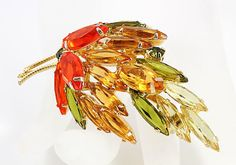 Spectacular display of colors in this circa 1960s leaf brooch. It showcases navette and marquis open back rhinestones in fabulous autumn shades of