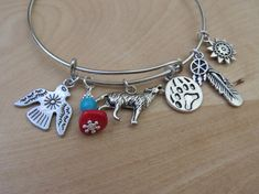 ~Welcome to my listing~  Southwestern Native American themed Expandable Bangle  This expandable bracelet can be worn individually or with other bracelets One size fits all and a great addition to any jewellery box!  Fully adjustable slide on silver plated wire charm bangle bracelet With 6 charms with Coral and Turquoise beads  The charms are Thunder Bird, Wolf, Bear Paw Print, Dream Catcher, Feather and Sun  These charms are beautiful Tibetan silver If there are any charms that you would…