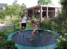lowered trampoline in a family garden in the netherlands in the background a covered outdoor space wooden structure painted pale grey - Garden Design With Trampoline