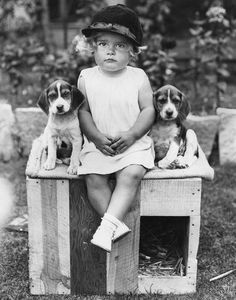 1930's. Little girl and her beagles.