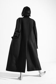 Minimal + classic- camera shy in a black coat- the model faces forward with her back to the lens- simple- minimal- classic