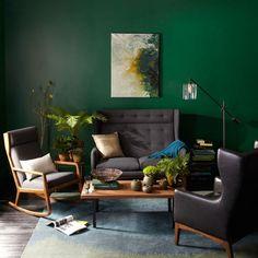Neste ambiente criado pela West Elm, um tom escuro de verde cobre toda a parede e serve como pano de fundo dramático e aconchegante para que poltronas com ares de aconchego se reúnam. Com estofamentos cinza e pretos, elas ganham a companhia de folhagens em um clima selvagem.