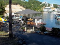 Wahoo commercial multi-slip aluminum floating boat dock with corrugated metal hip roof. Floating aluminum deck features shaded outbuilding, connected to shore by flat gangways with aluminum rails.