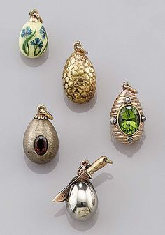 A COLLECTION OF ANTIQUE RUSSIAN MINIATURE EGG PENDANTS. Comprising: a gold egg with reeded design centring a mixed oval-cut peridot accented with diamonds; a gold and silver egg set with a garnet; an enamel egg with painted corn flowers; a gold egg of textured design, and a novelty egg of silver with a gold knife.
