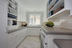 Amazing laundry room features open shelving suspended over an enclosed washer and dryer.