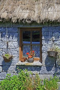Casa no campo na Irlanda. Telhado de palha, paredes de pedra e flores na janela.