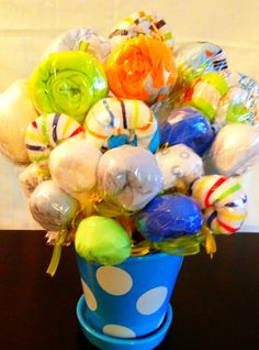 DIY Baby gift wrapping - find a cute flower pot, roll baby onesies and towels insert 3/16 wood rods, wrap the rod and baby gift in cellophane. Twist the cellophane at the base of the rolled gift. Secure with tape and  add bow!
