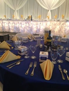 White backdrop and head table with royal blue satin guest tables and buttercup satin napkins made this wedding stunning!