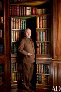 Businessman Pierre Bergé at the secret door that leads to his primary living quarters downstairs | archdigest.com