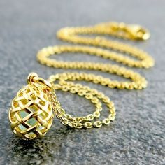 Weave Small Egg Pendant in Gold Vermeil, with a piece of Blue Topaz rough gemstone inside.