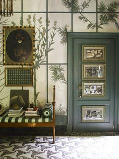 The Castellini House in Milan features a seaweed green and off-white color scheme. Love the botanical mural  and framed art on the door. Great design details.
