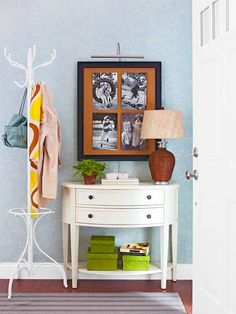 This entry is modest, but doesn't feel small or stuffy. With two wide drawers and a shelf of baskets beneath (perfect for gloves and mittens), a small demilune cabinet offers a surprising amount of storage capacity. A freestanding coatrack adds a bit of vintage charm to the space while a collage of photographs instills personality.