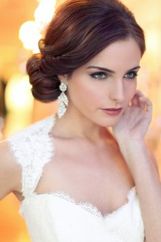 neat and low side bun. big crystal earrings and queen ann wedding dress.