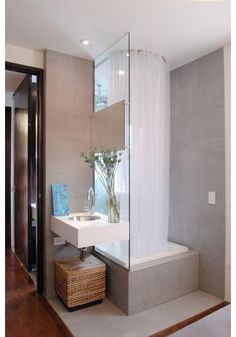 A shower doesn't have to be huge to be wonderful. I love this light-filled shower-and-tub combo. The gossamer-thin white shower curtain on a ceiling track is a pretty look, plus it accommodates those who are modest.